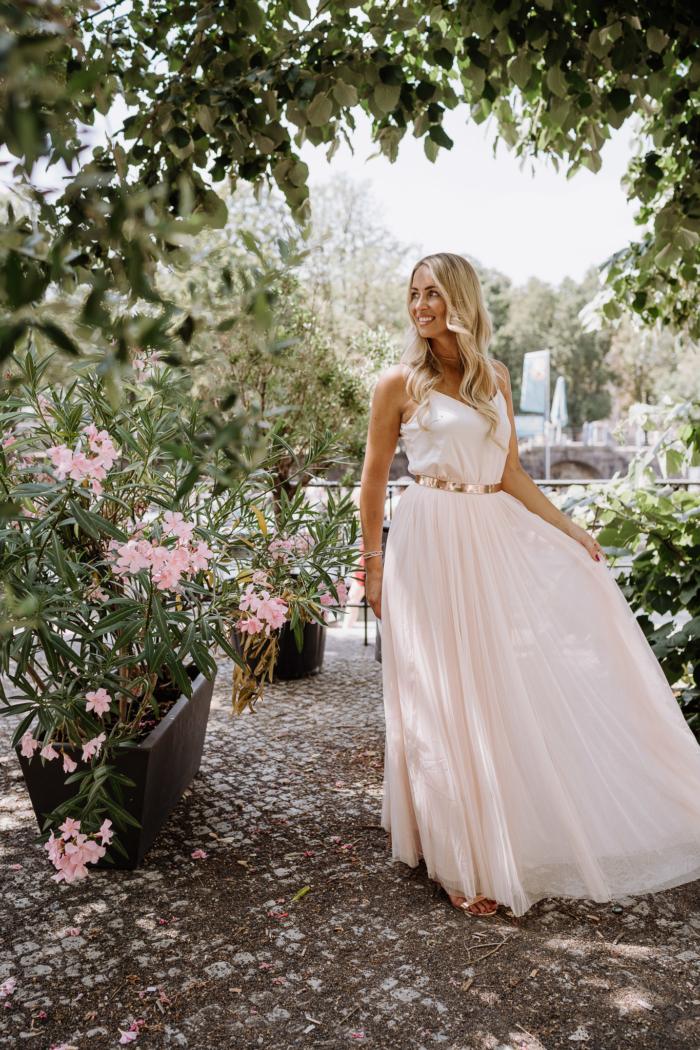 Frau in rosafarbenem Brautkleid zwischen Bäumen