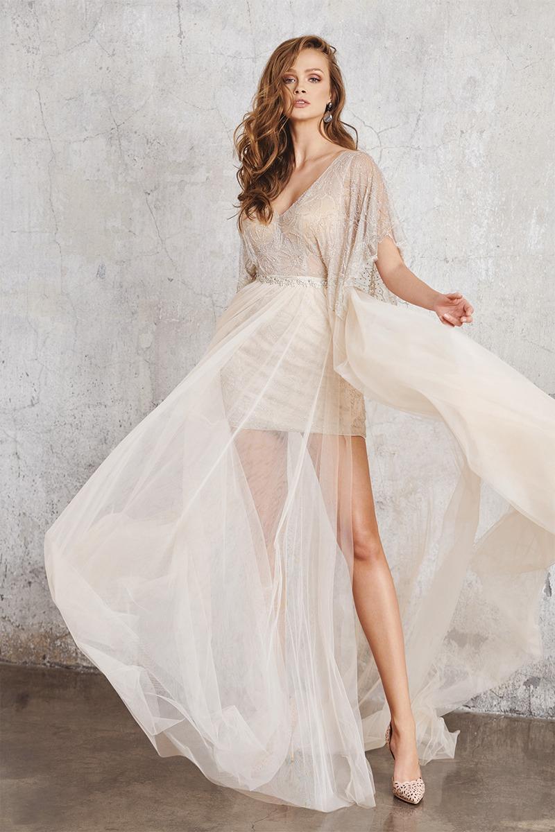 Frau in kurzem Hochzeitskleid mit einem durchsichtigen Überrock